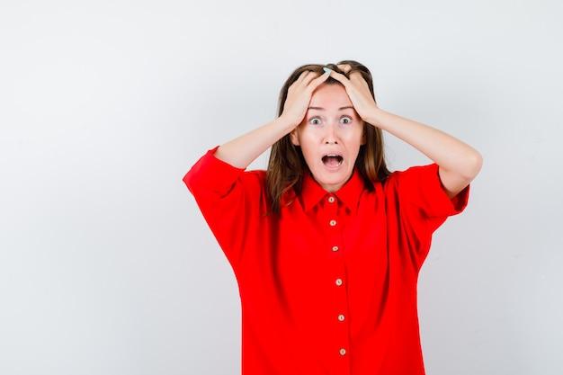 Jonge vrouw in rode blouse met handen op het hoofd en angstig, vooraanzicht.