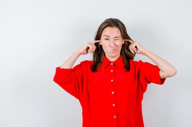 Jonge vrouw in rode blouse met vingers in de oren en weemoedig, vooraanzicht.