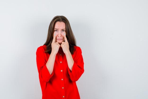 Jonge vrouw in rode blouse wijzend op haar tranen en depressief kijken, vooraanzicht.
