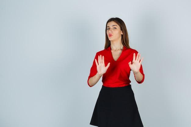 Jonge vrouw in rode blouse, zwarte rok die beperkingsgebaar toont en er schattig uitziet