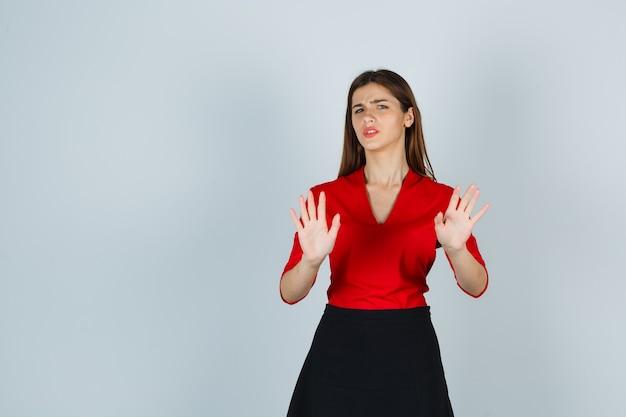Jonge vrouw in rode blouse, zwarte rok die beperkingsgebaar toont en ontevreden kijkt