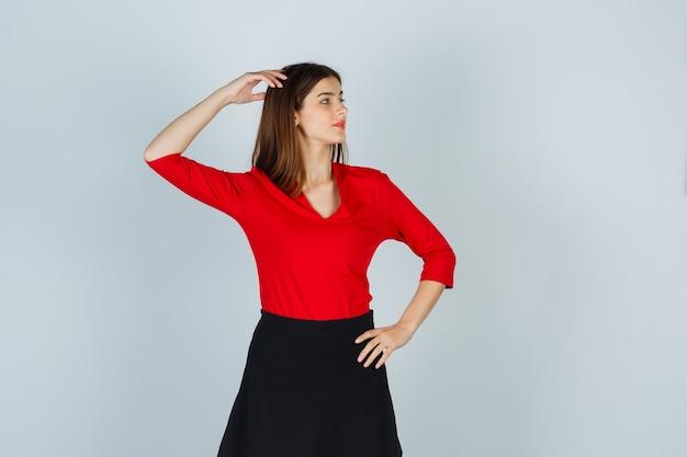 Jonge vrouw in rode blouse, zwarte rok die één hand op hoofd houdt