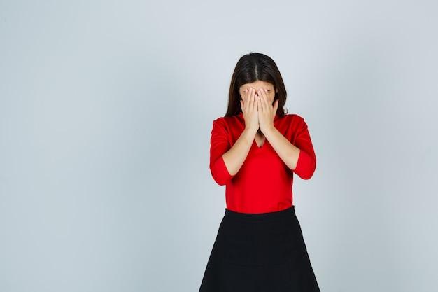 Jonge vrouw in rode blouse, zwarte rok die gezicht bedekt met handen en beschaamd kijkt