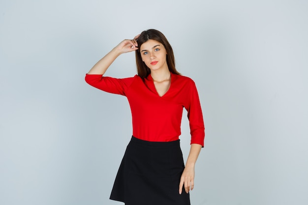 Jonge vrouw in rode blouse, zwarte rok die hand op hoofd houdt