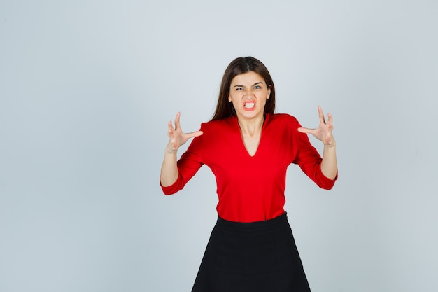 Jonge vrouw in rode blouse, zwarte rok die handen op boze manier opheft en boos kijkt