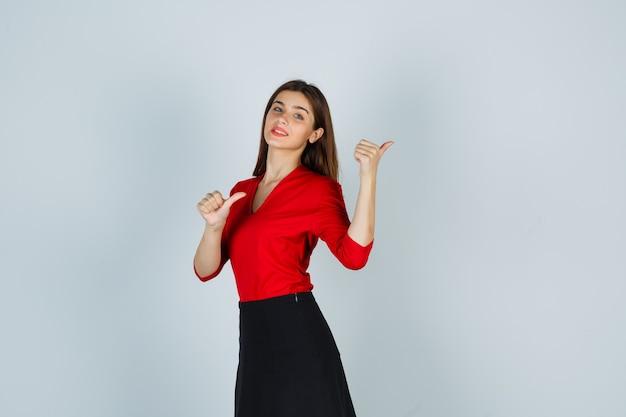 Jonge vrouw in rode blouse, zwarte rok die met duimen opzij richt en er schattig uitziet