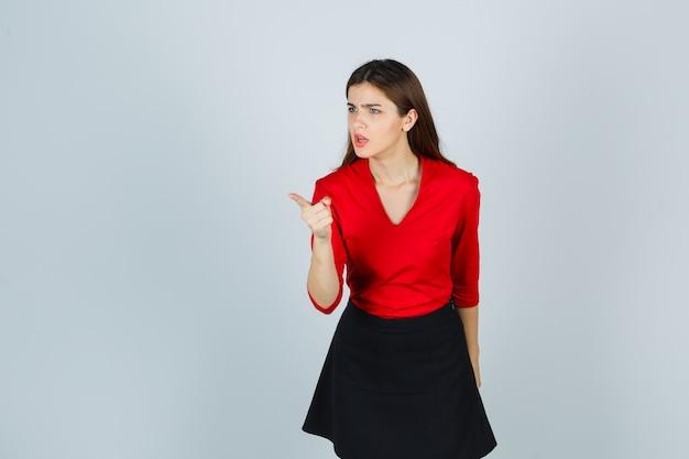 Jonge vrouw in rode blouse, zwarte rok die met wijsvinger richt