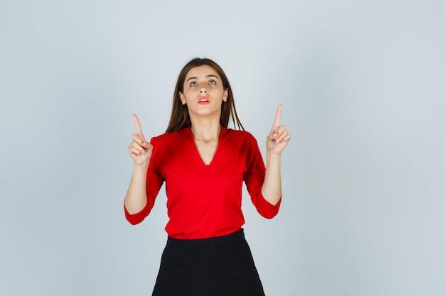 Jonge vrouw in rode blouse, zwarte rok die met wijsvingers benadrukt en gericht kijkt