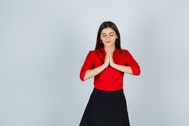 Jonge vrouw in rode blouse, zwarte rok die namaste-gebaar toont en kalm kijkt