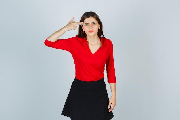 Jonge vrouw in rode blouse, zwarte rok die pistoolgebaar dichtbij hoofd toont en boos kijkt