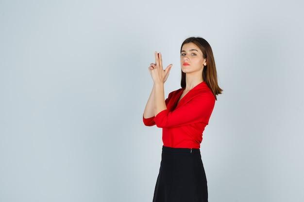 Jonge vrouw in rode blouse, zwarte rok die pistoolgebaar toont en zelfverzekerd kijkt