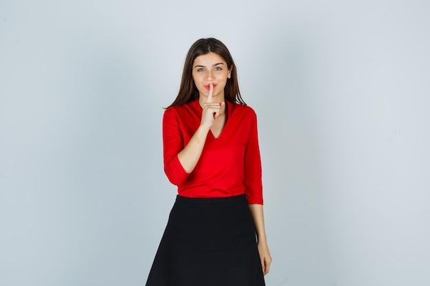 Jonge vrouw in rode blouse, zwarte rok die stiltegebaar toont en er schattig uitziet