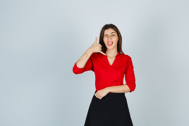 Jonge vrouw in rode blouse, zwarte rok die telefoongebaar toont