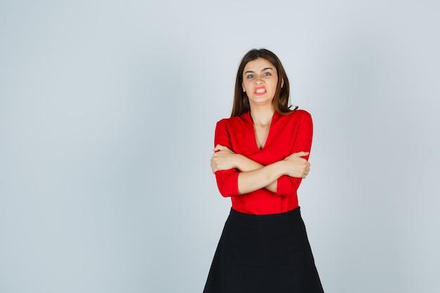 Jonge vrouw in rode blouse, zwarte rok staande armen gekruist en boos kijkt