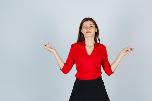 Jonge vrouw in rode blouse, zwarte rok staande in mediterende pose