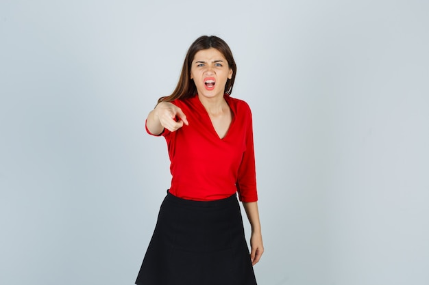 Jonge vrouw in rode blouse, zwarte rok wijzend op camera met wijsvinger