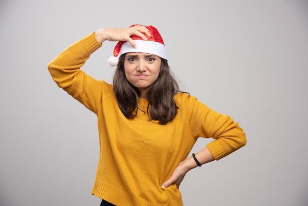 Jonge vrouw in rode hoed van de kerstman die over een witte muur stelt.