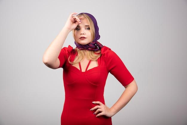 Jonge vrouw in rode jurk camera kijken.