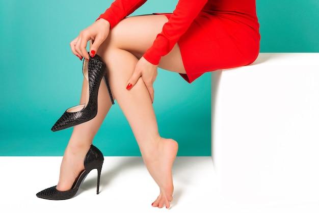 Jonge vrouw in rode jurk die lijden aan pijn in het been in kantoor vanwege ongemakkelijke schoenen - afbeelding