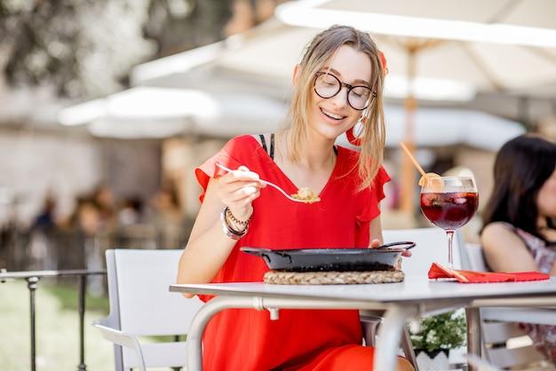 Jonge vrouw in rode jurk die zee paella eet, traditionele valenciaanse rijstschotel, buiten zitten in het restaurant in valencia, spanje