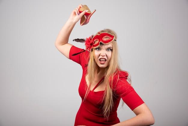 Jonge vrouw in rode jurk gooit haar hiel.