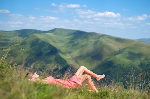 Jonge vrouw in rode jurk liggen op groen grasveld rusten op een zonnige dag in zomer bergen genieten van uitzicht op de natuur.