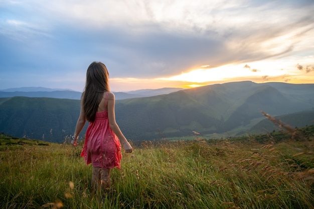 Jonge vrouw in rode jurk lopen op grasveld op een winderige avond in herfst bergen.