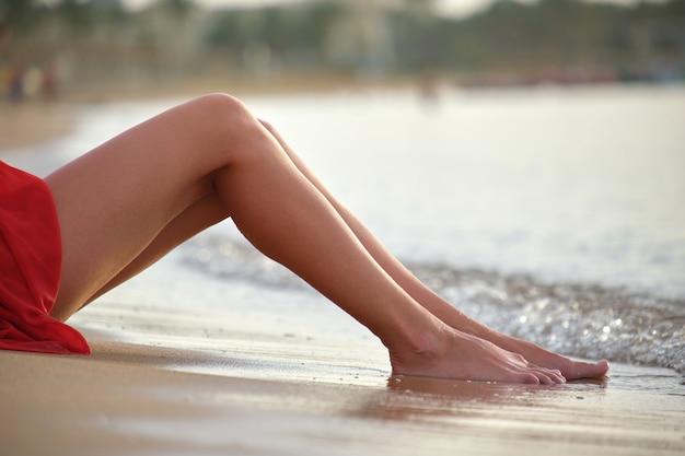 Jonge vrouw in rode jurk met blote benen ontspannen op zandstrand aan zee genieten van warme tropische ochtend.
