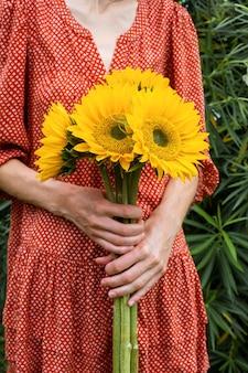 Jonge vrouw in rode jurk met een groot boeket zonnebloemen