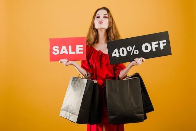 Jonge vrouw in rode jurk met verkoop 40% teken en papieren boodschappentassen geïsoleerd over geel