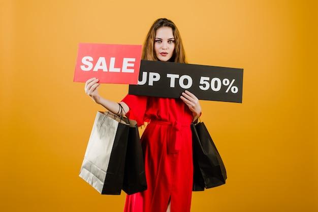 Jonge vrouw in rode jurk met verkoop tot 50% teken en papieren boodschappentassen geïsoleerd over geel