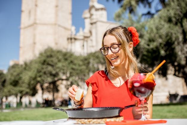 Jonge vrouw in rode jurk met zee paella, traditionele valenciaanse rijstschotel, buiten zitten in het restaurant in het centrum van de oude stad van valencia