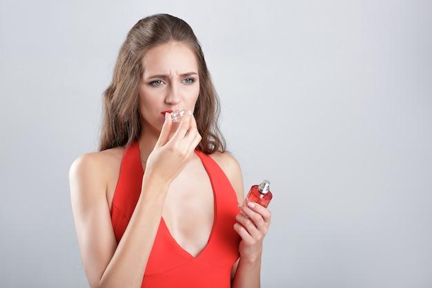Jonge vrouw in rode jurk ruikende parfum. onaangename geur