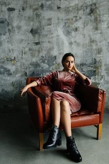 Jonge vrouw in rode jurk zittend op lederen stoel in loft interieur