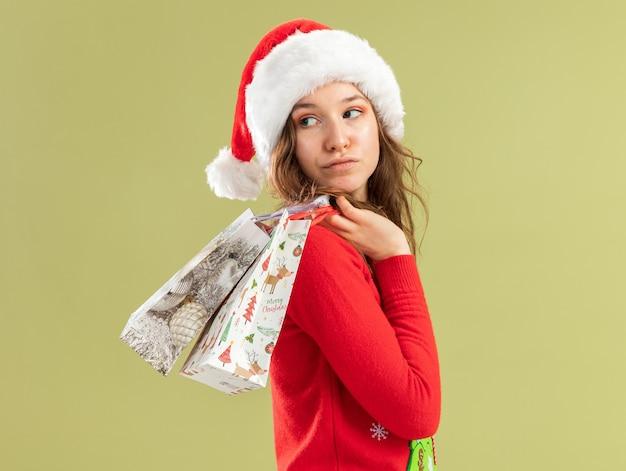 Jonge vrouw in rode kerst trui en kerstmuts met papieren zakken met kerstcadeaus terugkijkend met zelfverzekerde uitdrukking