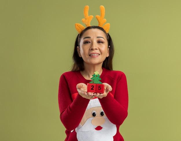 Jonge vrouw in rode kerstmissweater die grappige rand met hertenhoorns dragen die stuk speelgoed kubussen met datum vijfentwintig tonen die met het gelukkige gezicht glimlachen kijken