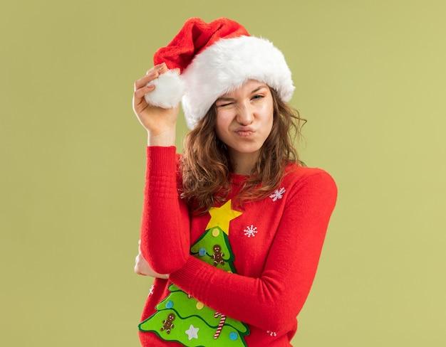 Jonge vrouw in rode kerstmissweater en santahoed spelen met hoed op zoek knipogen