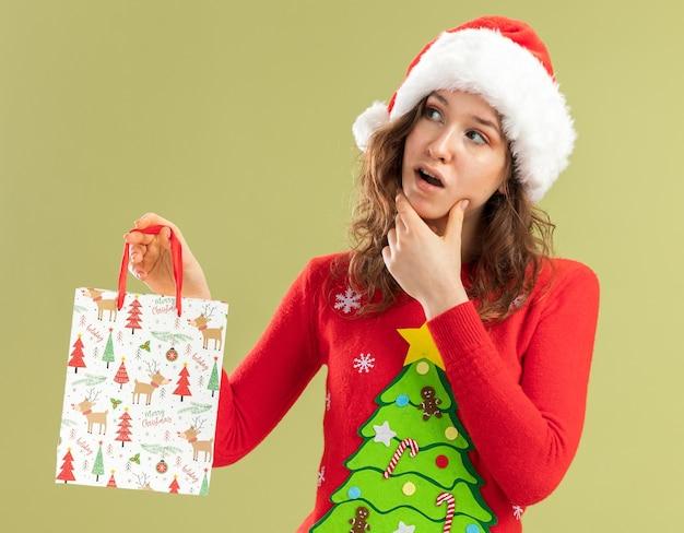 Jonge vrouw in rode kerstsweater en kerstmuts met papieren zak met kerstcadeaus opzij kijkend verbaasd over groene muur