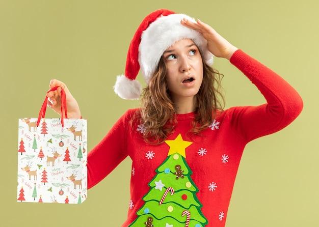 Jonge vrouw in rode kersttrui en kerstmuts die een papieren zak met kerstcadeaus vasthoudt en verbaasd opkijkt terwijl ze over de groene muur staat