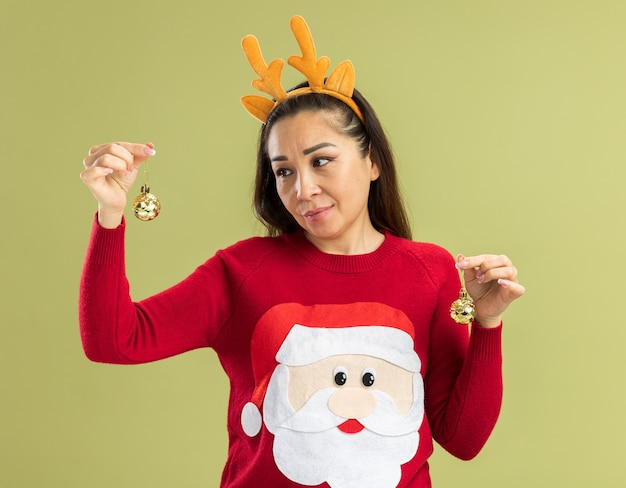 Jonge vrouw in rode kersttrui met een grappige rand met hertenhoorns die kerstballen vasthoudt en naar de bal kijkt met een glimlach op het gezicht die een keuze probeert te maken die over de groene muur staat