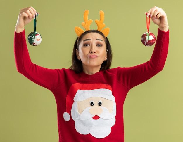 Jonge vrouw in rode kersttrui met een grappige rand met hertenhoorns die kerstballen vasthoudt met een blij gezicht over de groene muur