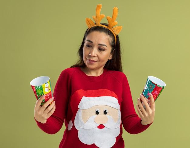 Jonge vrouw in rode kersttrui met een grappige rand met hertenhoorns die kleurrijke papieren bekers vasthoudt en er verward uitziet en probeert een keuze te maken die over de groene muur staat