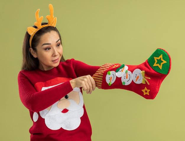 Jonge vrouw in rode kersttrui met grappige rand met hertenhoorns die kerstsok vasthoudt en er geïntrigeerd uitziet over groene muur