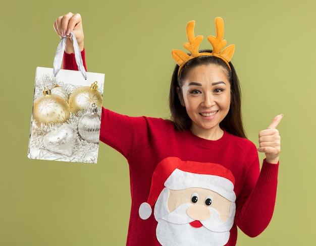Jonge vrouw in rode kersttrui met grappige rand met hertenhoorns en papieren zak met kerstcadeau met glimlach op het gezicht met duimen omhoog over groene muur