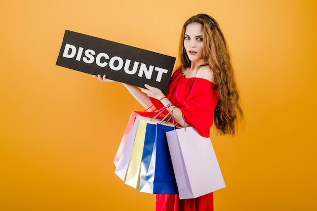 Jonge vrouw in rode kleding met kortingsteken en kleurrijke die het winkelen zakken over geel wordt geïsoleerd