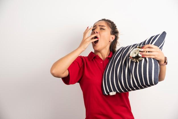 Jonge vrouw in rode korte broek met een wekker en met een kussen.