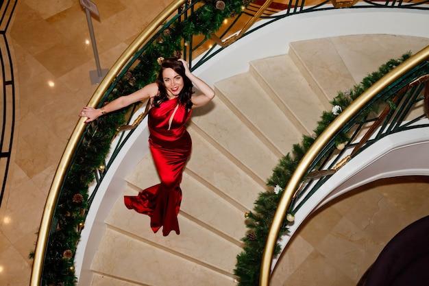 Jonge vrouw in rode lange jurk op trap versierd voor kerstmis of nieuwjaar. mooie dame in luxe cocktailjurk klimt trappen van haar huis. leuningen in kerstboomtakken. ruimte kopiëren