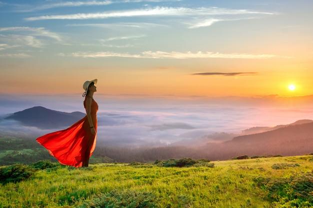 Jonge vrouw in rode lange jurk staande op een berg