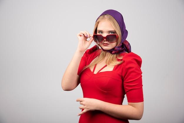 Jonge vrouw in rode outfit poseren op grijze achtergrond.