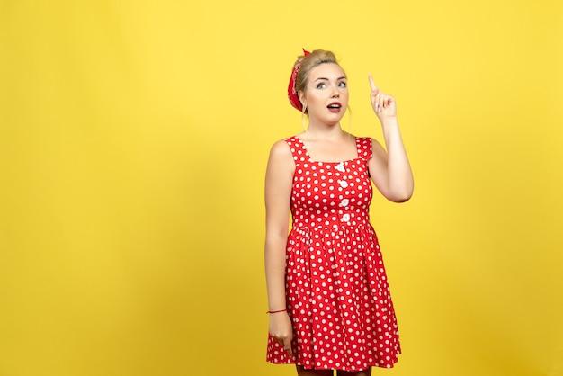 Jonge vrouw in rode polka dot jurk denken op geel